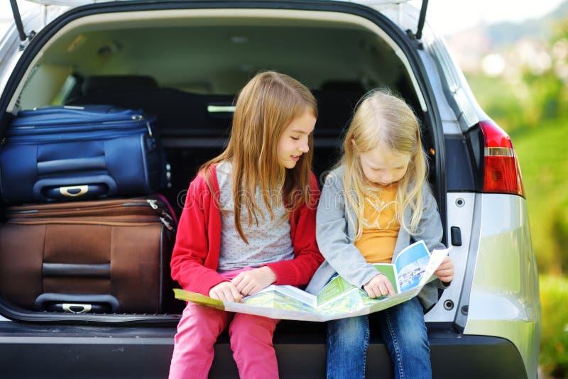 Dos niñas adorables listas para ir el vacaciones con sus padres Niños que se sientan en un coche que examina un mapa imagen de archivo