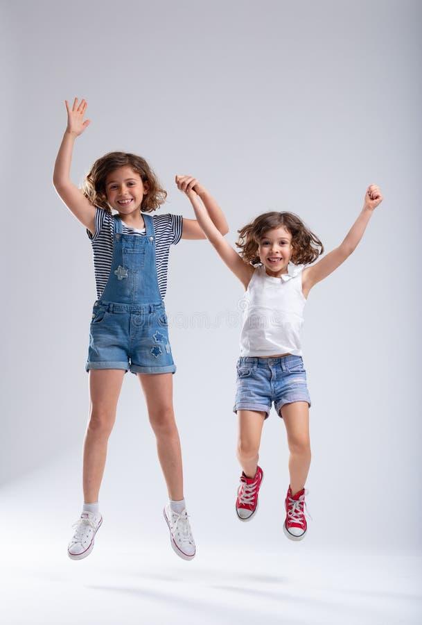 Dos niñas animadas vivaces que saltan junto foto de archivo libre de regalías