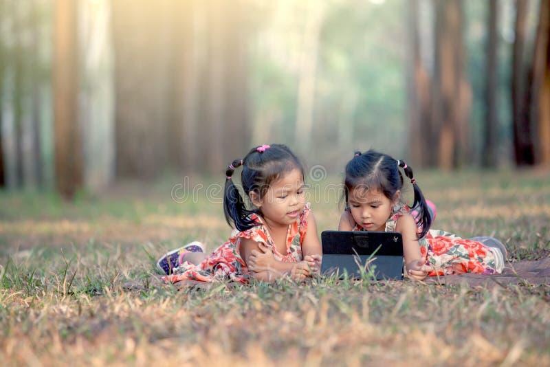 Dos niñas asiáticas que mienten en la hierba y que usan la tableta foto de archivo