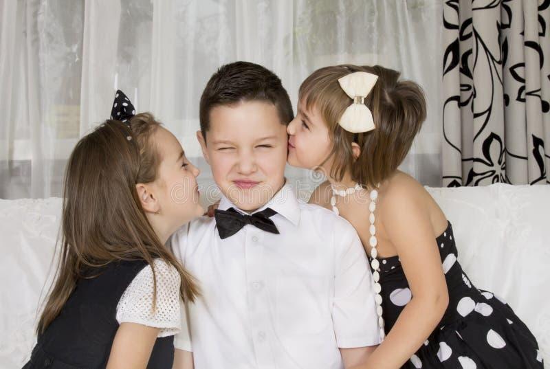 Dos niñas besan al muchacho hermoso imagenes de archivo