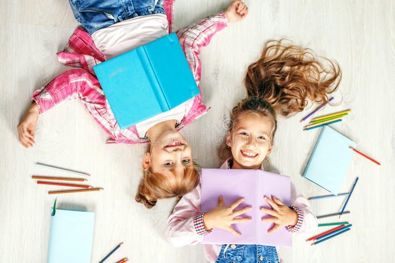 Dos niñas divertidas con los libros Endecha plana el concepto de niños foto de archivo