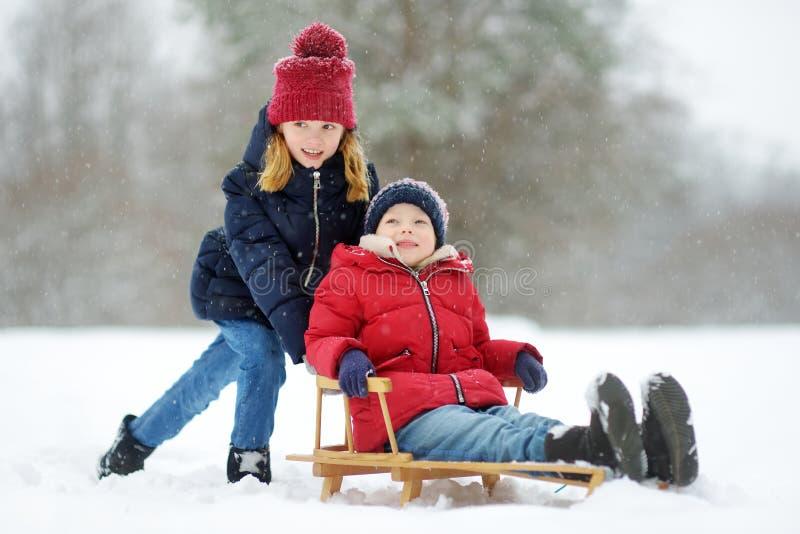 Dos niñas divertidas que se divierten con un trineo en parque hermoso del invierno Niños lindos que juegan en una nieve fotografía de archivo