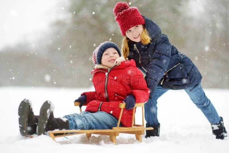 Dos niñas divertidas que se divierten con un trineo en parque hermoso del invierno Niños lindos que juegan en una nieve imagen de archivo