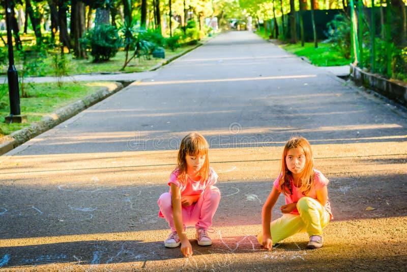 Dos niñas drowing con tiza en el parque imagenes de archivo