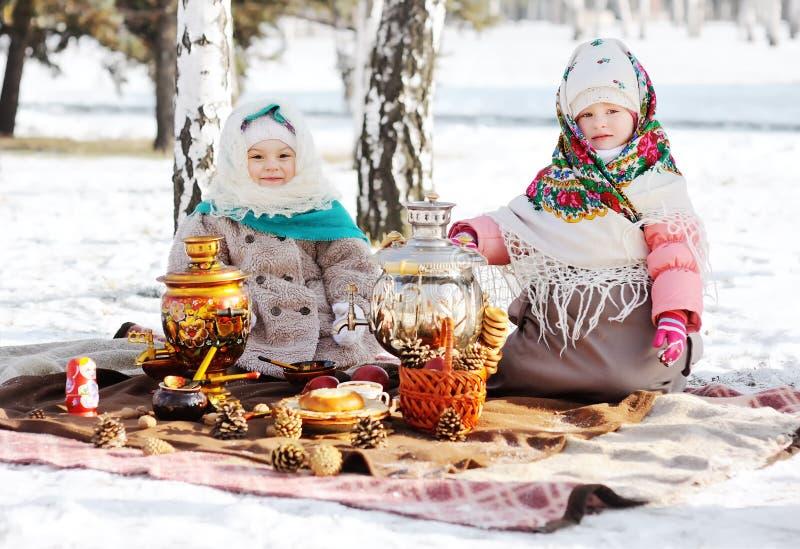 Dos niñas en abrigos de pieles y mantones en el estilo ruso en su cabeza contra la perspectiva de un samovar foto de archivo libre de regalías
