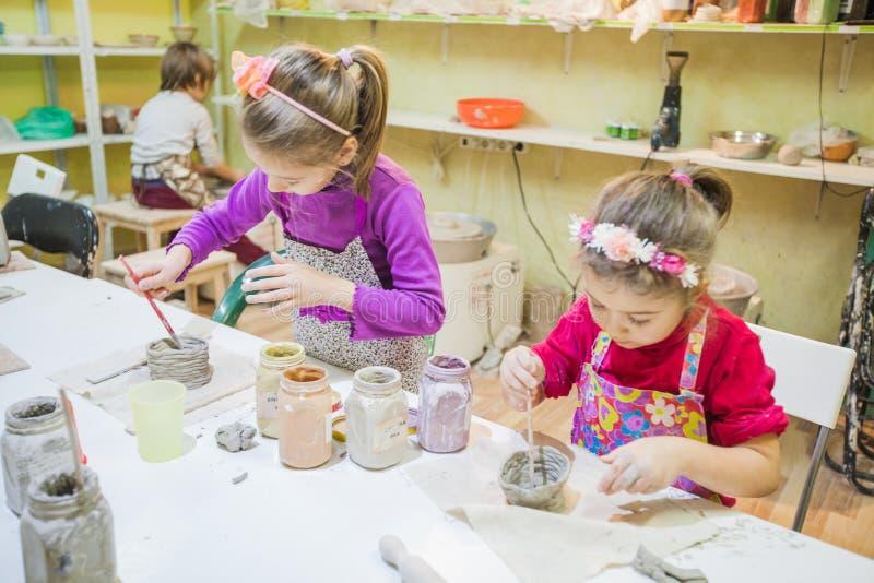 Dos niñas en el taller de la cerámica que pinta a Clay Vase foto de archivo libre de regalías
