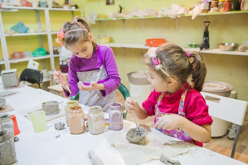 Dos niñas en el taller de la cerámica que pinta a Clay Vase imágenes de archivo libres de regalías