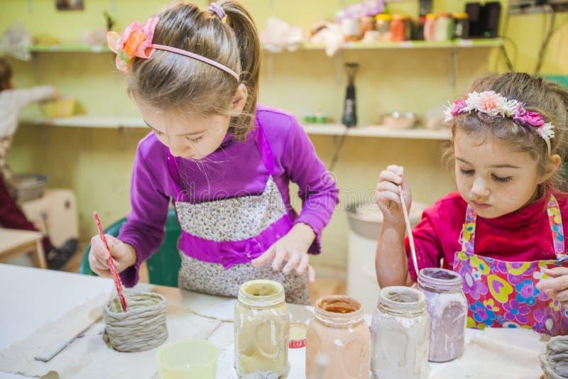 Dos niñas en el taller de la cerámica que pinta a Clay Vase fotografía de archivo