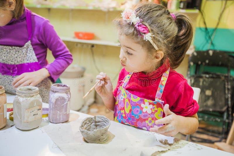 Dos niñas en el taller de la cerámica que pinta a Clay Vase imagen de archivo
