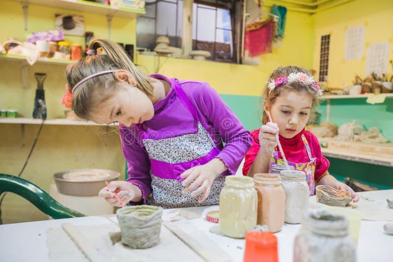 Dos niñas en el taller de la cerámica que pinta a Clay Vase fotos de archivo libres de regalías