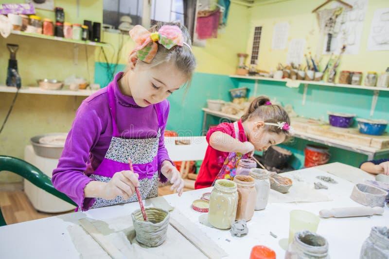 Dos niñas en el taller de la cerámica que pinta a Clay Vase fotografía de archivo libre de regalías