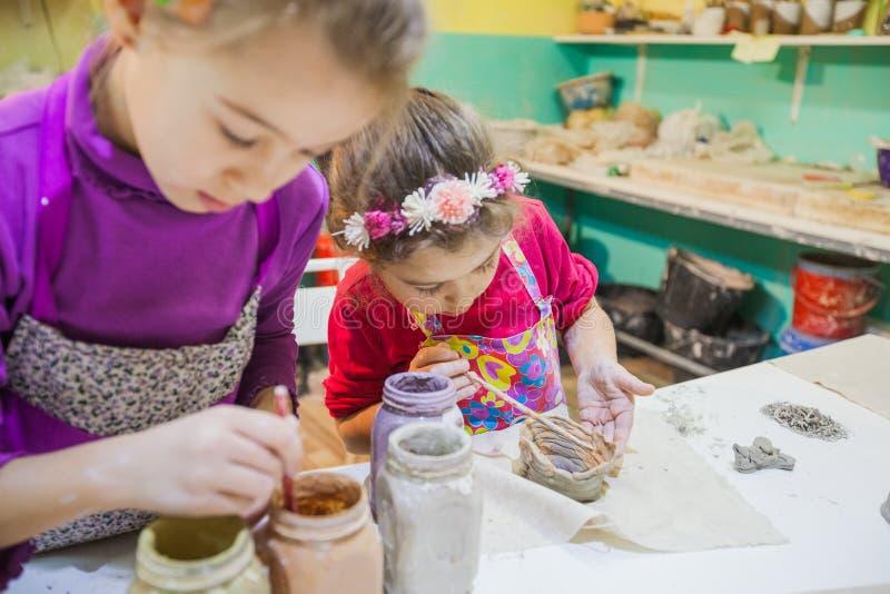 Dos niñas en el taller de la cerámica que pinta a Clay Vase foto de archivo