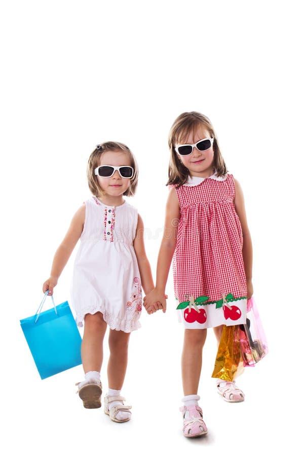 Dos niñas en gafas de sol y bolsos de compras fotos de archivo