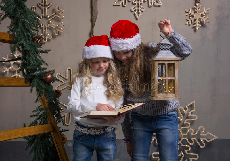 Dos niñas en los casquillos de Papá Noel están leyendo un libro en una casa fotografía de archivo libre de regalías