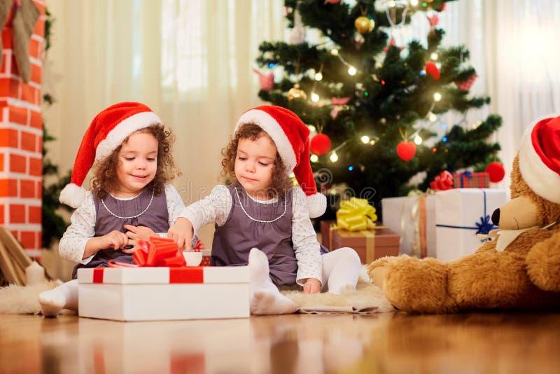 Dos niñas en los casquillos de Santa Claus que se sientan en el ingenio del piso imagenes de archivo