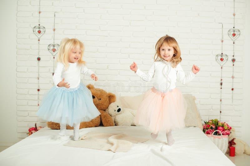 Dos niñas en vestidos agradables en la diversión que salta en una cama foto de archivo libre de regalías