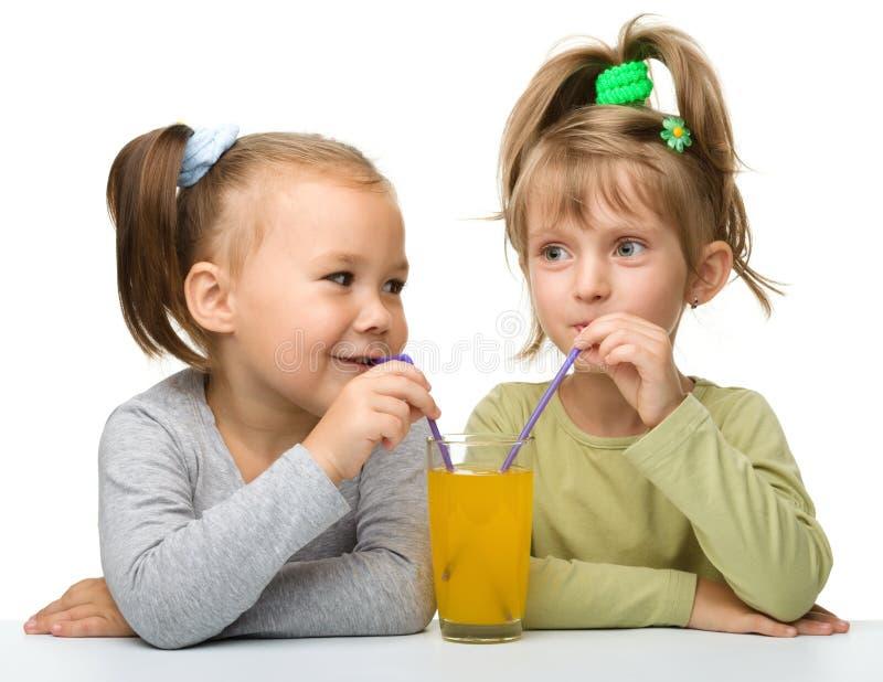 Dos niñas están bebiendo el zumo de naranja imagen de archivo