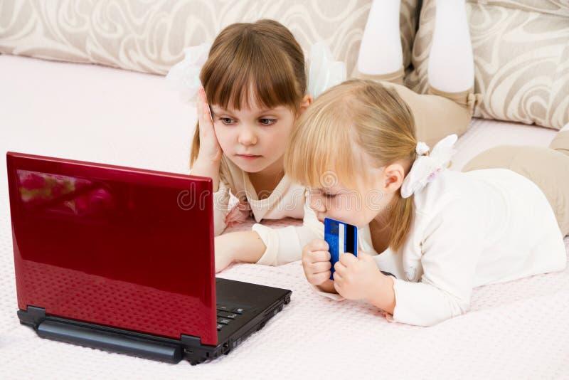 Dos niñas están con una computadora portátil fotografía de archivo