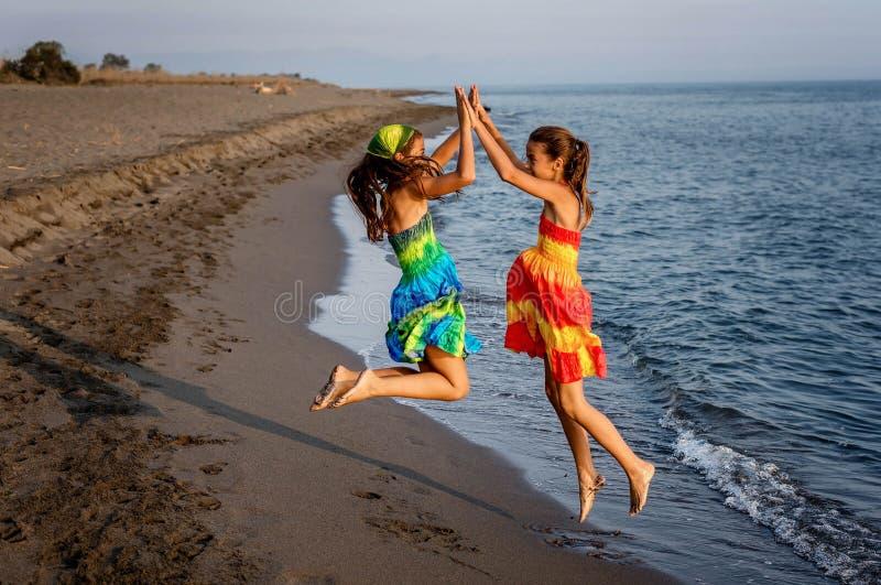 Dos niñas felices que saltan en el aire en la playa fotografía de archivo libre de regalías