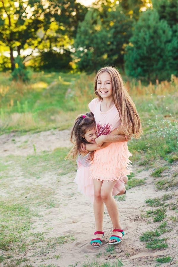 Dos niñas felices que se divierten y que lo abrazan en el verano soleado imágenes de archivo libres de regalías