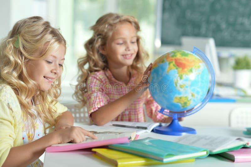 Dos niñas hermosas en el libro de lectura de la clase y mirada imagenes de archivo