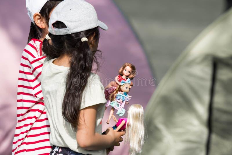 Dos niñas jovenes que se sostienen y que juegan con sus muñecas plásticas foto de archivo