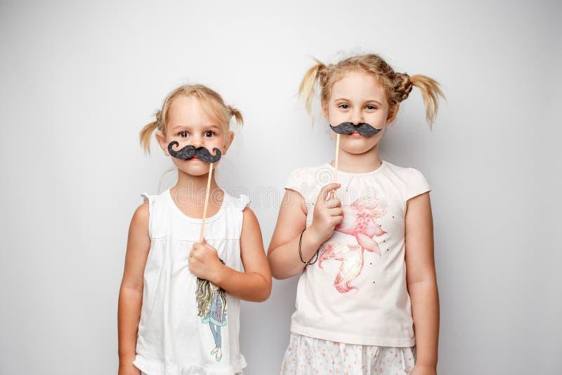 Dos niñas lindas con los bigotes de papel mientras que presenta contra el fondo blanco fotos de archivo