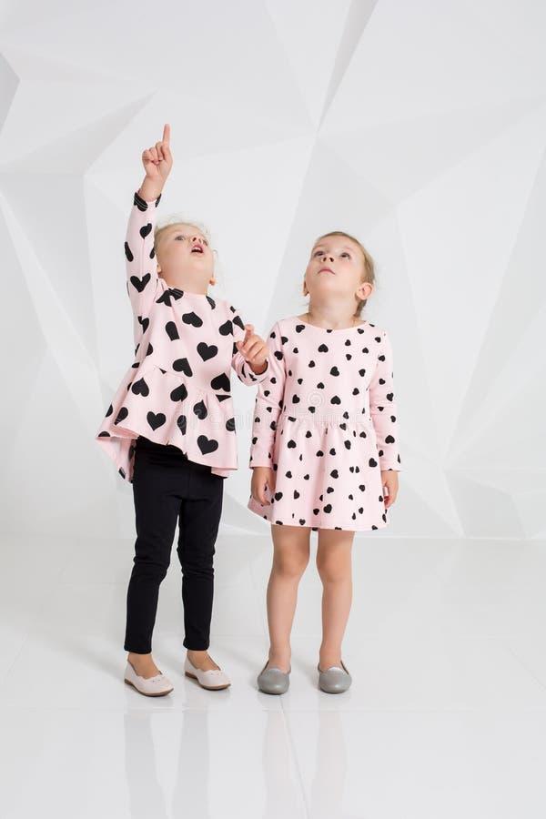 Dos niñas lindas que se colocan en ropa rosada con los corazones negros en el fondo blanco de la pared en el estudio imagen de archivo libre de regalías