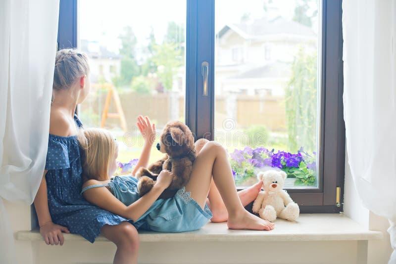 Dos niñas pequeñas europeas lindas que se sientan en travesaño cerca de ventana fotografía de archivo libre de regalías