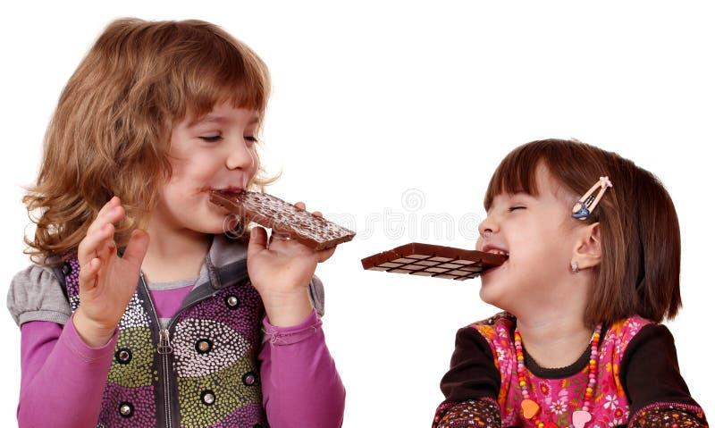 Dos niñas que comen el chocolate foto de archivo