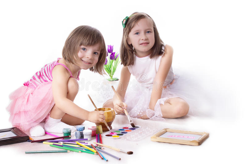 Dos niñas que dibujan con la pintura foto de archivo