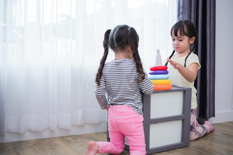 Dos niñas que juegan pequeñas bolas del juguete en hogar juntas Educa imagen de archivo libre de regalías