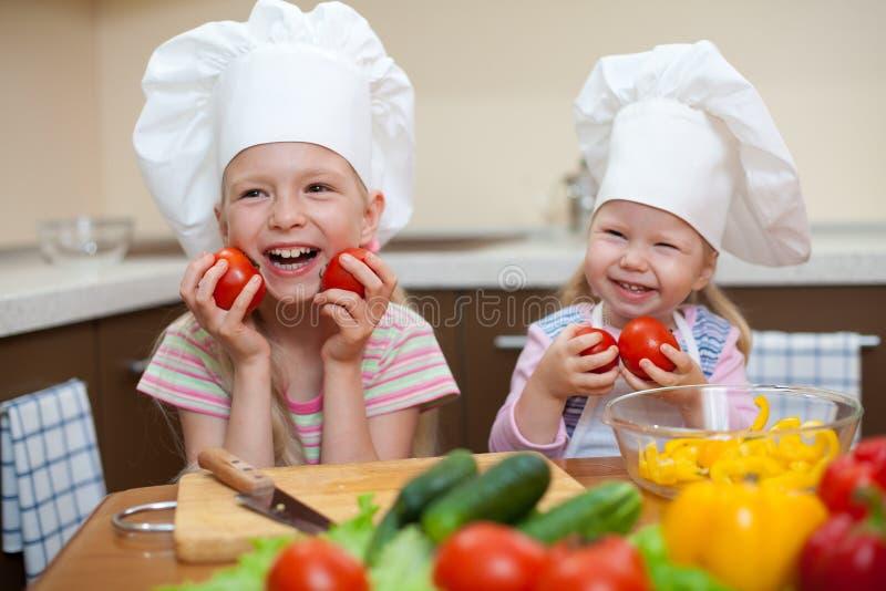 Dos niñas que preparan el alimento sano en cocina imagen de archivo