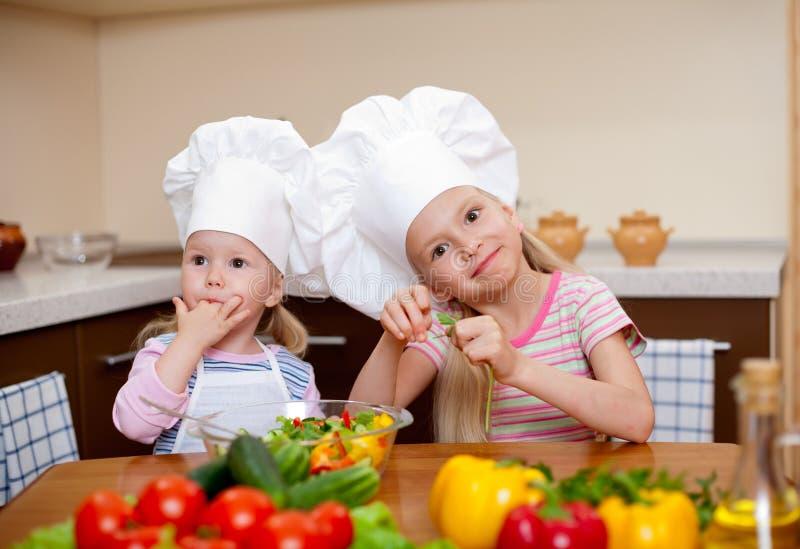 Dos niñas que preparan el alimento sano en cocina fotografía de archivo libre de regalías