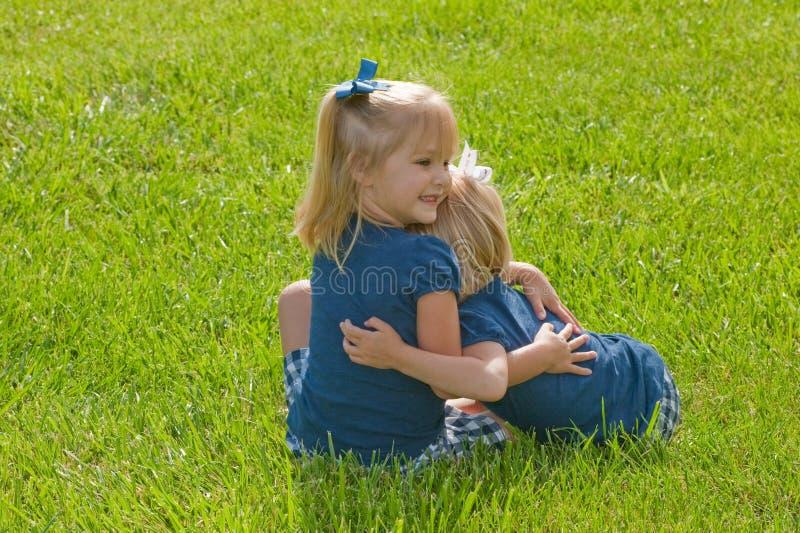 Dos niñas que se sientan en el abrazo de la hierba imágenes de archivo libres de regalías