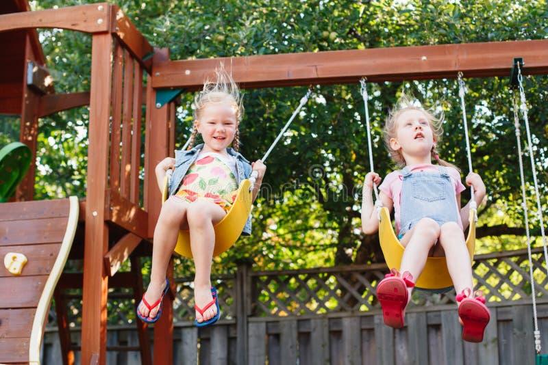 Dos niñas sonrientes felices en el oscilación en patio del patio trasero afuera el día de verano foto de archivo