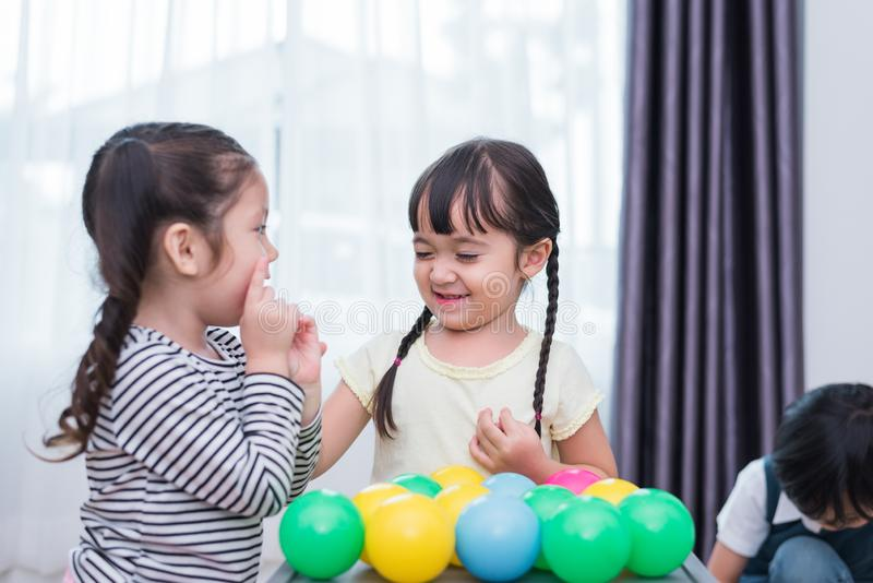 Dos niñas y muchacho que juegan pequeñas bolas del juguete en hogar juntas Concepto de la forma de vida de la educaci?n y de la f imagenes de archivo