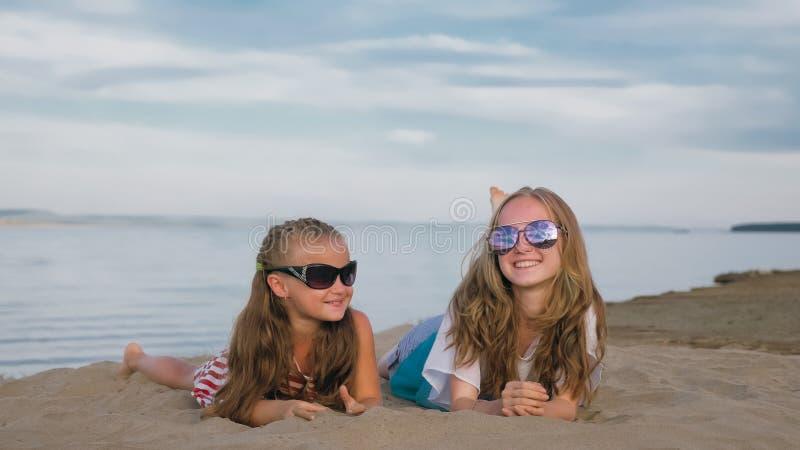 Dos niños adolescentes se están sentando en la playa fotografía de archivo libre de regalías