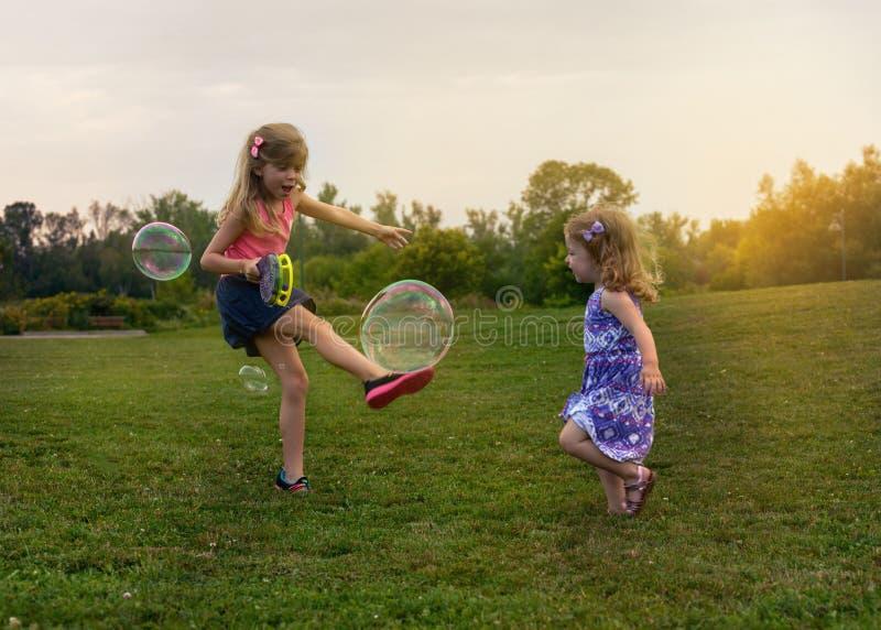 Dos niños adorables están jugando con las burbujas de jabón en el campo imagenes de archivo