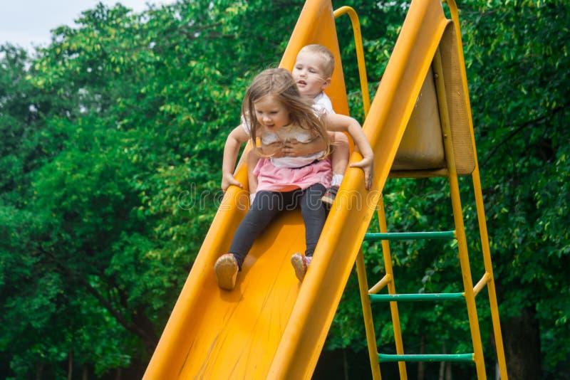 Dos niños alegres ruedan abajo la diapositiva amarilla en el patio y el grito a una velocidad emocionante foto de archivo libre de regalías