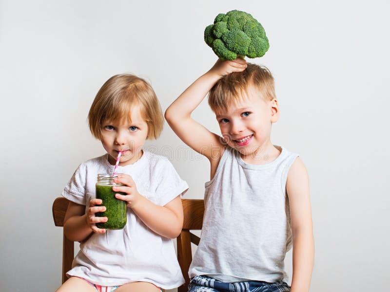 Dos niños bonitos de la diversión con los smoothies y el bróculi verdes Helthy foto de archivo