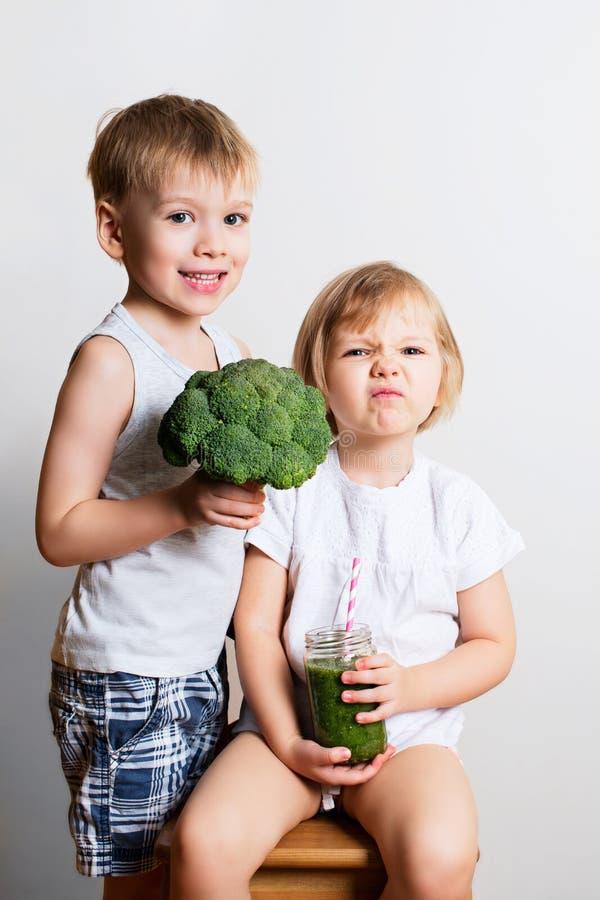 Dos niños bonitos de la diversión con los smoothies y el bróculi verdes sobre blanco imágenes de archivo libres de regalías