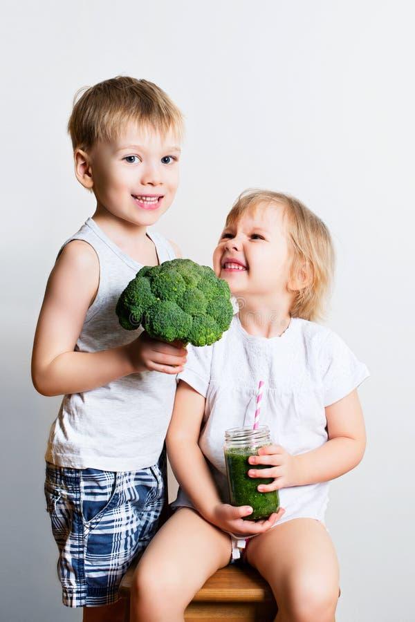 Dos niños bonitos de la diversión con los smoothies y el bróculi verdes sobre blanco fotografía de archivo