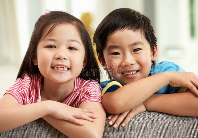 Dos niños chinos que se relajan en el sofá en el país imagen de archivo libre de regalías