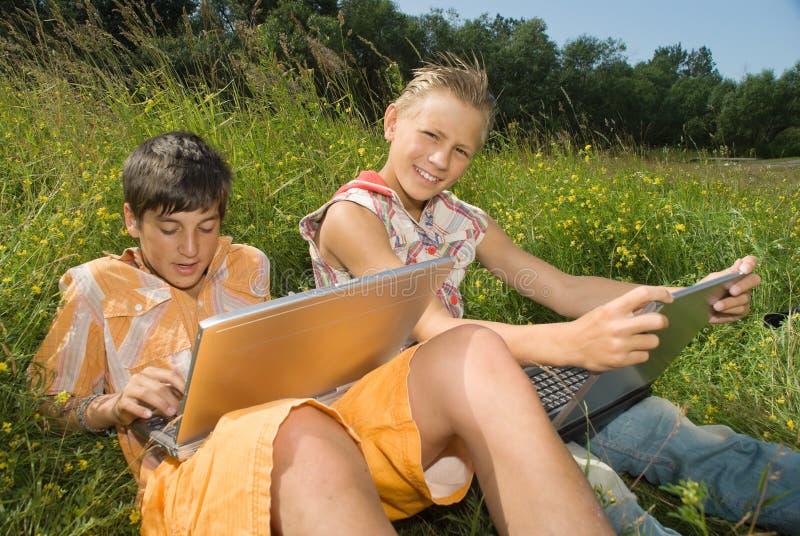 Dos niños con la computadora portátil imagenes de archivo
