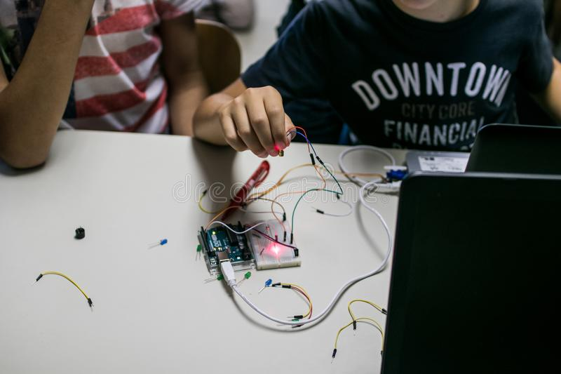 Dos niños construyen un circuito del prototipo con un control rojo del laser fotos de archivo