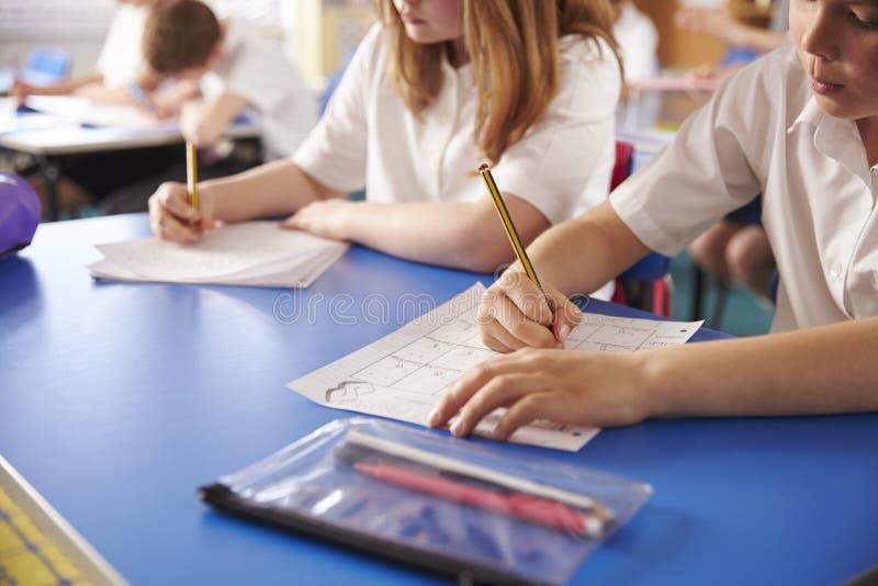 Dos niños de la escuela primaria que trabajan en la clase, cosecha cercana foto de archivo libre de regalías
