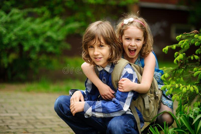 Dos niños de una edad de escuela más joven, el muchacho y la muchacha, agazapado abrazando imagen de archivo libre de regalías