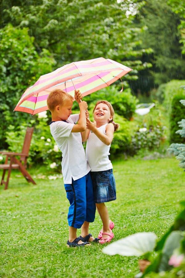 Dos niños debajo del paraguas en lluvia foto de archivo libre de regalías