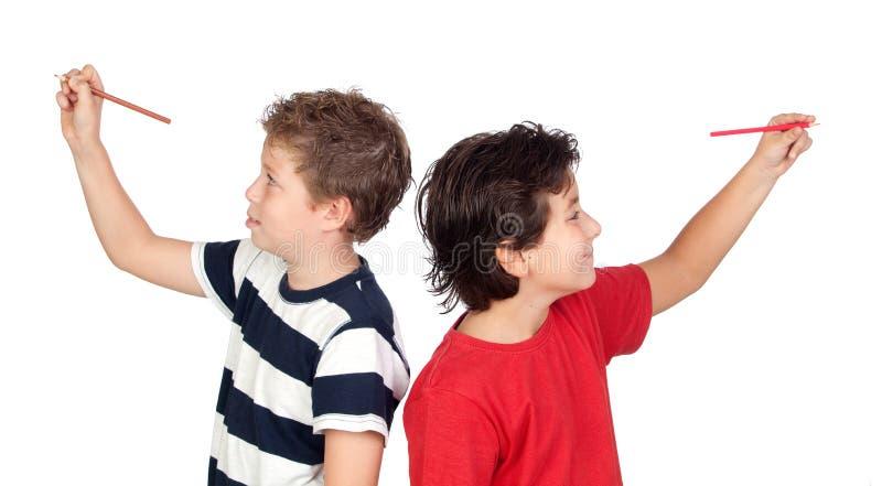 Dos niños del estudiante que escriben algo imagen de archivo libre de regalías